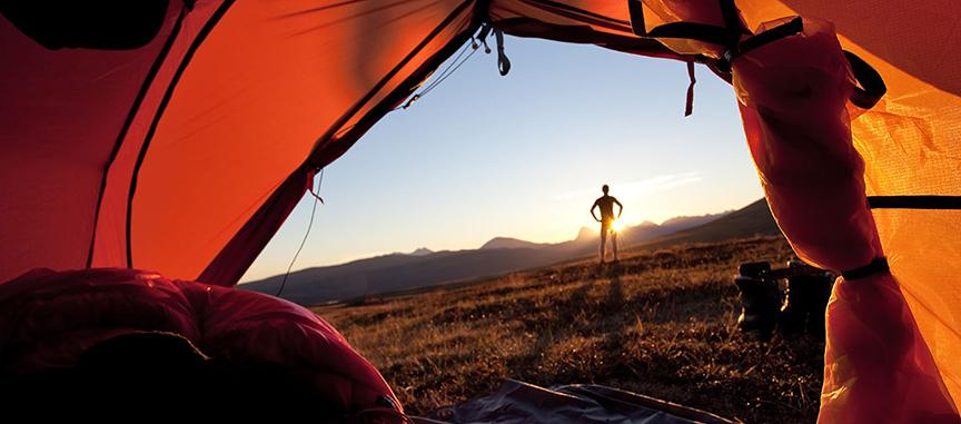 View from inside a tent of a sunrise and a man standing