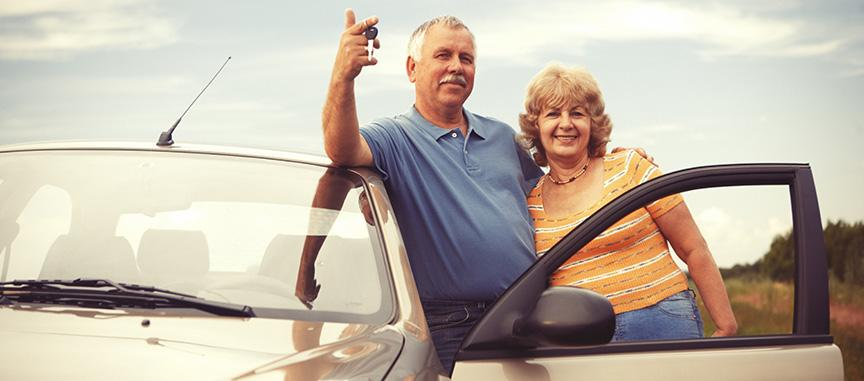 Middle-aged couple leaning on a car holding car keys