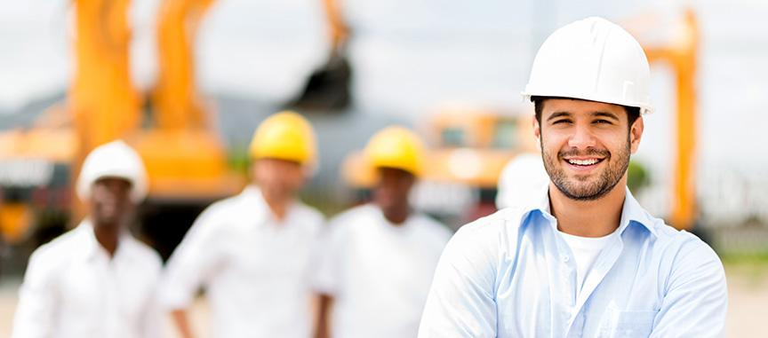 Smiling construction worker in front of a group of other construction workers
