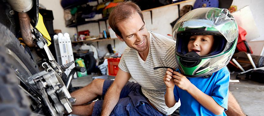 Father and young son working on a motocycle