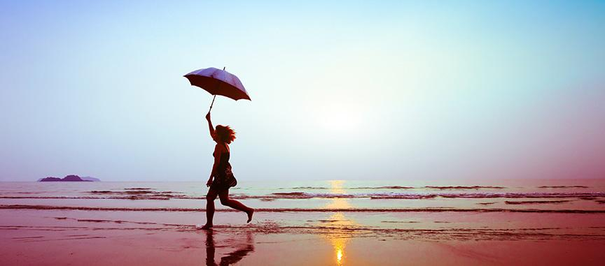 Women running on the beach at sunset holding an umbrella
