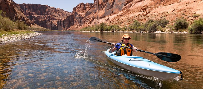 Active women kayaking in a bright canyon