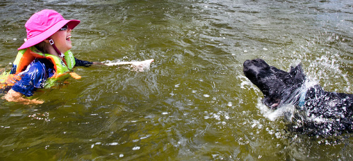 Young girl swimming in the Yellowstone River with a black lab