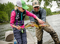 Girl and fishing guide catching a brown trout