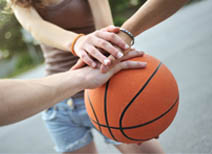 three people's hands on a basketball